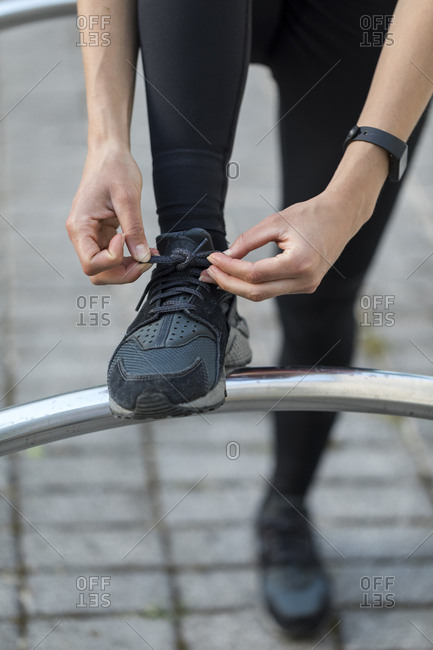 Young woman ties her athletic shoes during an outdoor workout