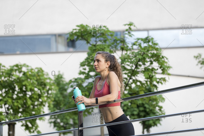 Young woman drinking water after a an outdoor workout