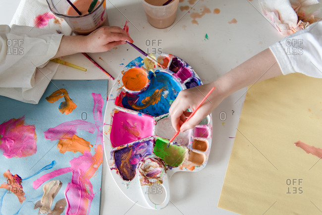 Top view of little kids dipping paintbrushes at art table