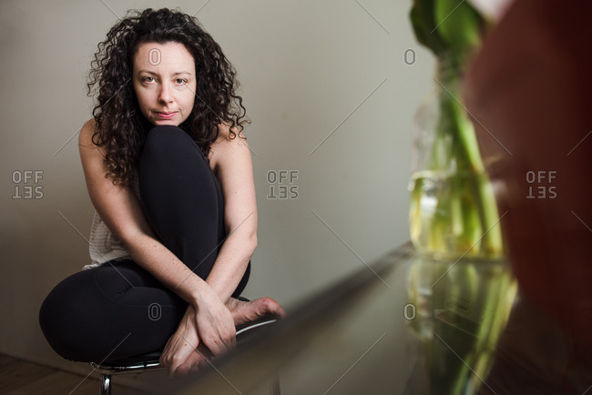 Portrait of brunette woman in leggings at home