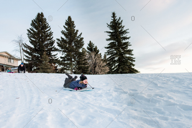 Excited girl sledding down snowy hill