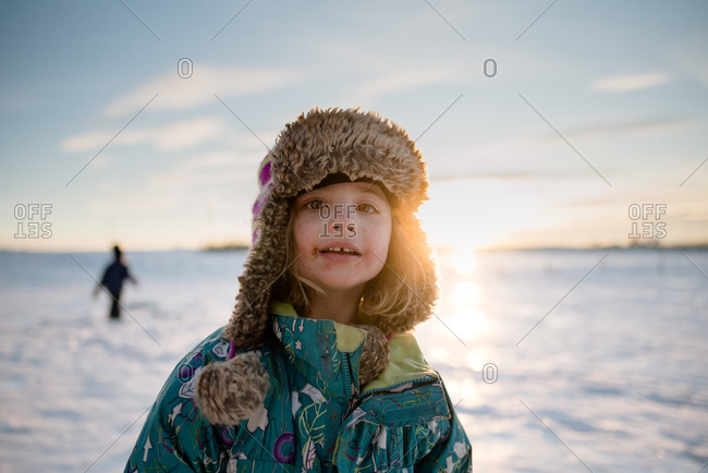 Portrait of toddler playing in the snow with fuzzy winter hat at sunset