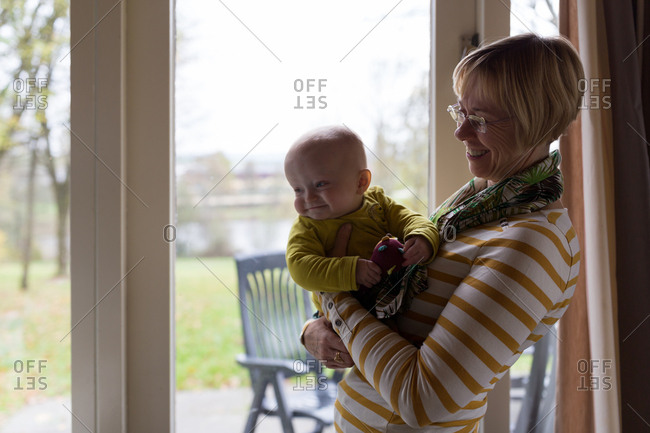 Happy and proud grandmother holding  baby boy at home
