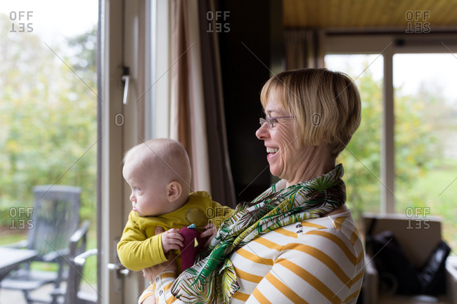 Happy grandmother and baby grandchild looking outside the window