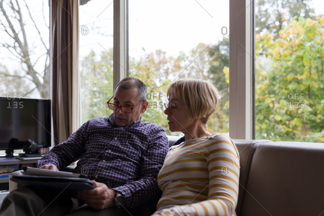 Senior couple looking at tablet computer together in homy sofa