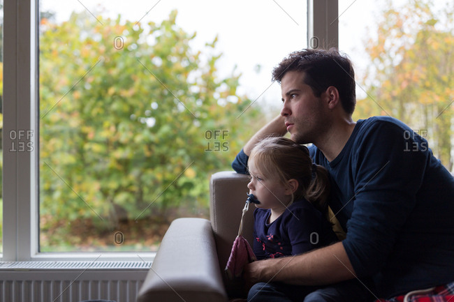 Father and daughter sitting in sofa watching television together
