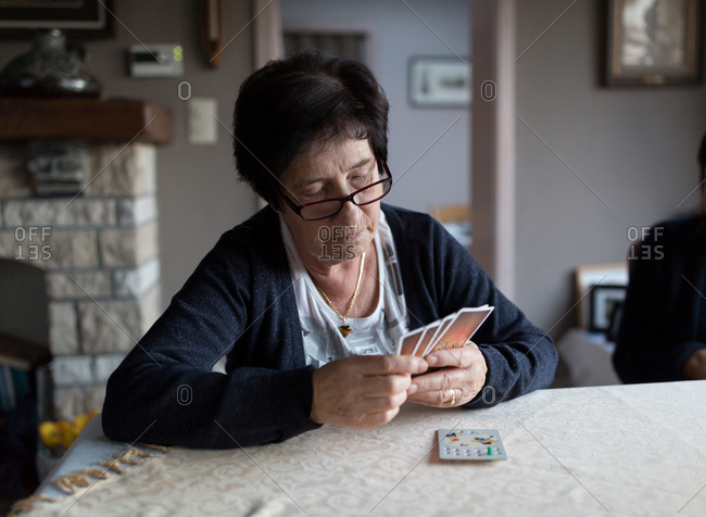 Senior woman holding deck of cards playing card game