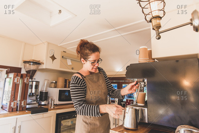 Woman using an espresso machine in a vintage coffee food truck