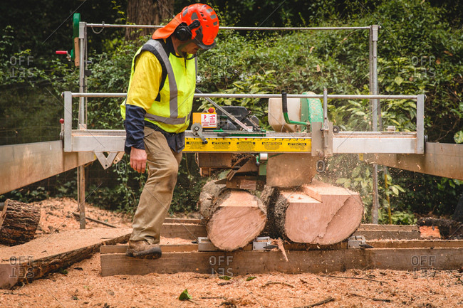 Man operating timber mill with safety gear