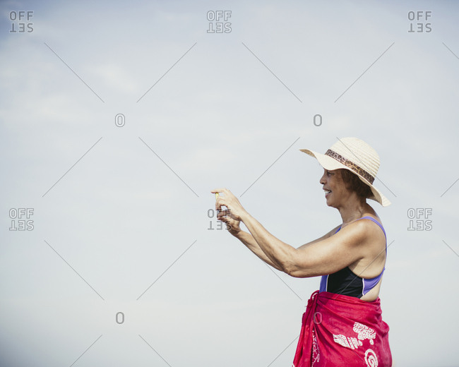 Senior woman in swimwear taking photo with smartphone at the beach