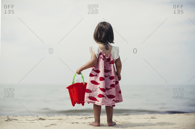 Rearview of little girl at beach holding bucket looking at the sea