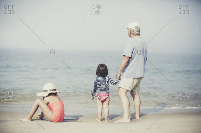 Rearview of grandpa holding granddaughter's hand as sister digs in the sand at beach