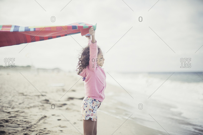 Young girl holding up towel blowing in the wind at the beach