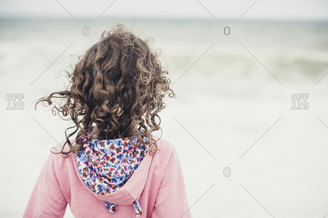 Rearview of little girl with curly hair looking at the sea on breezy day at the beach