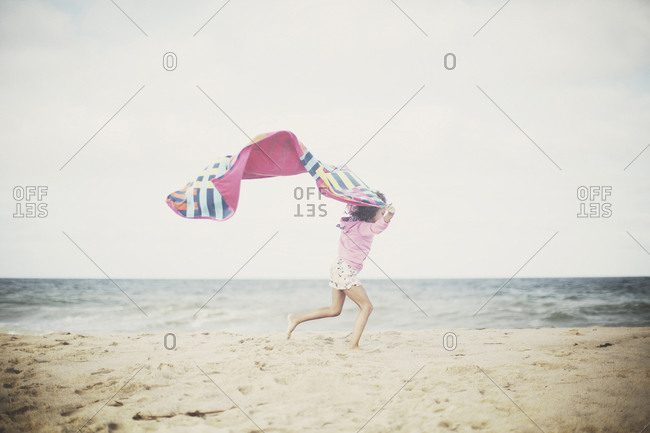 Young girl running along beach holding up towel blowing in the wind