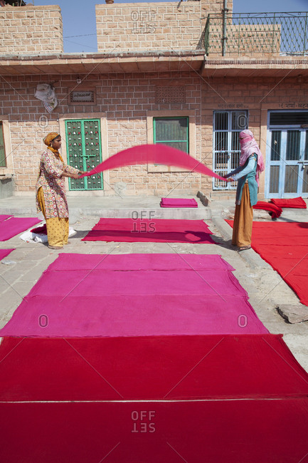 Jaipur, India - October 27, 2011: Women folding dyed red cloth at textile business