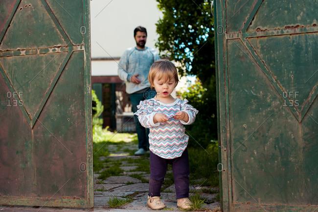 Dad following young girl walking in yard