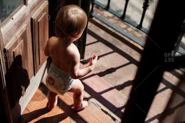 Baby standing in doorway with bright light