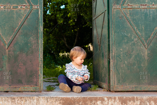 Baby sitting on concrete playing with card