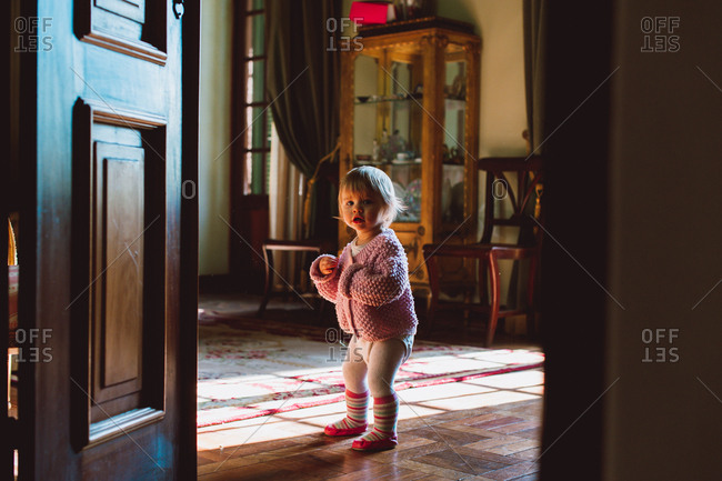 Little girl with curious look on her face standing in living room