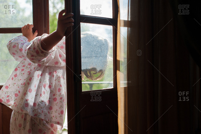 Little girl leaning out of front door