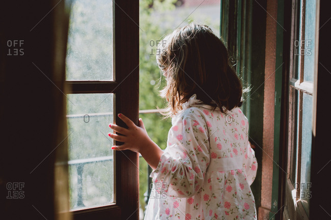 Young girl looking out on a balcony
