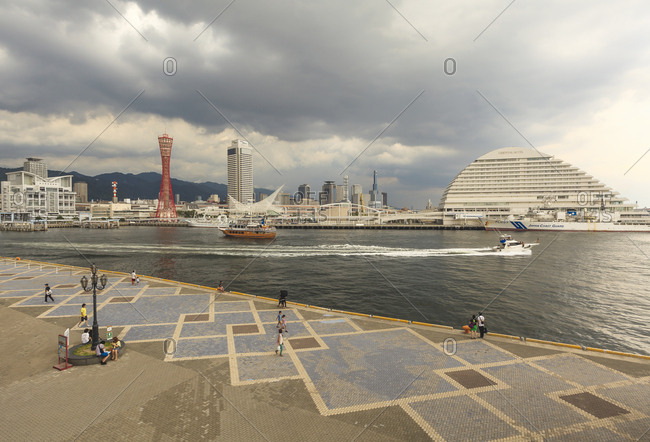 July 14, 2013: View of Takahama Wharf in Kobe Harborland before a storm at sunset. On the left is visible the red skyline Kobe Port Tower, Japan