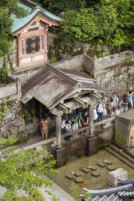 July 16, 2013: The Otowa Waterfall in the main hall of Kiyomizu-dera temple. Visitors use cups attached to long poles to drink from them. It's a Unesco World Heritage Site, Kyoto, Japan
