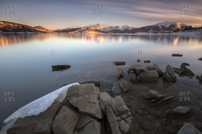 A tongue of ice to lap the shore of Campotosto lake at sunset, Gran Sasso and monti della Laga national park, Abruzzo, Italy