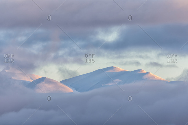 A clearing snowstorm reveal the peaks of the Gran Sasso mountain chain from Campotosto lake, Gran Sasso and Monti della Laga national park, Abruzzo, Italy