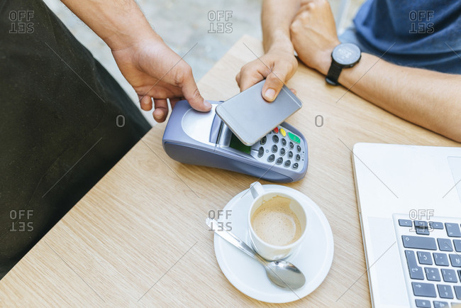 Man paying with his mobile phone at the bar