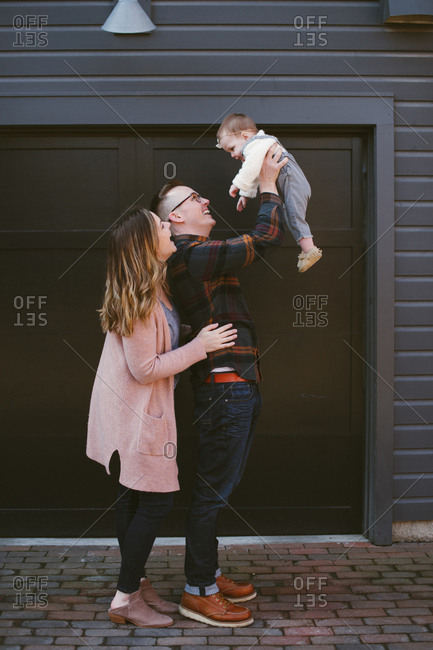Young couple smiling as dad holds baby daughter up in the air