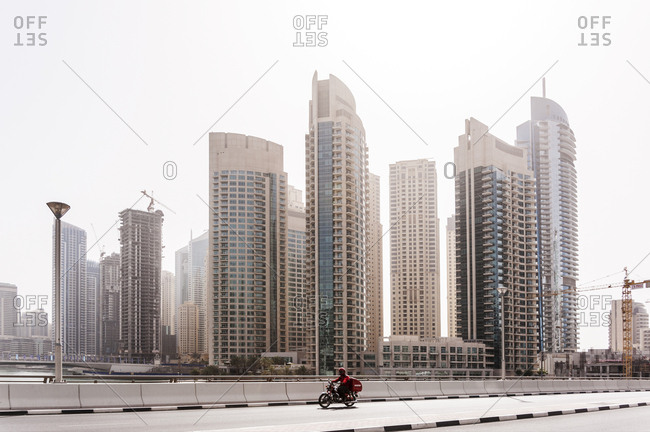 Dubai, United Arab Emirates - May 14, 2012: Delivery rider on motorbike dwarfed by towers and construction cranes in background
