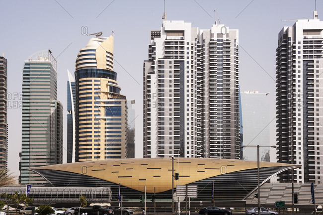 Dubai, United Arab Emirates - May 14, 2012: Traffic stopped in front of Metro rail station with office and residential buildings in the background