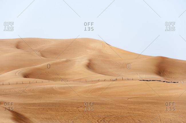 Vehicle tracks leading into the sand dunes in the desert of Dubai, United Arab Emirates