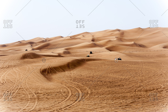 People riding all terrain vehicles in the sand dunes in the desert of Dubai, United Arab Emirates