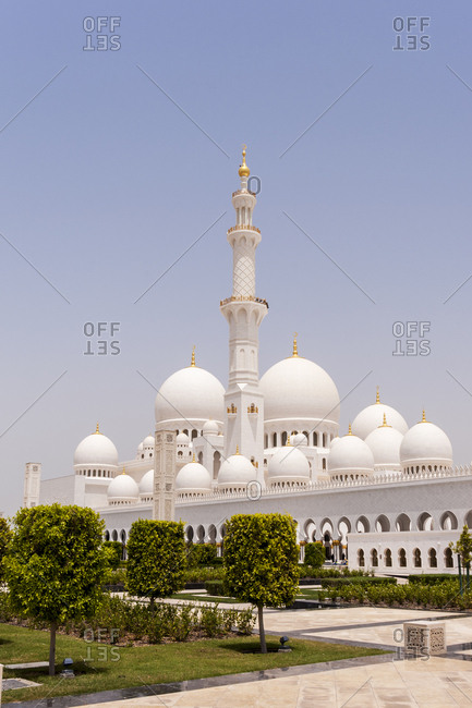 The landscaped gardens of the of the Sheikh Zayed Grand Mosque with the minarets and domes in the background in Abu Dhabi, United Arab Emirates