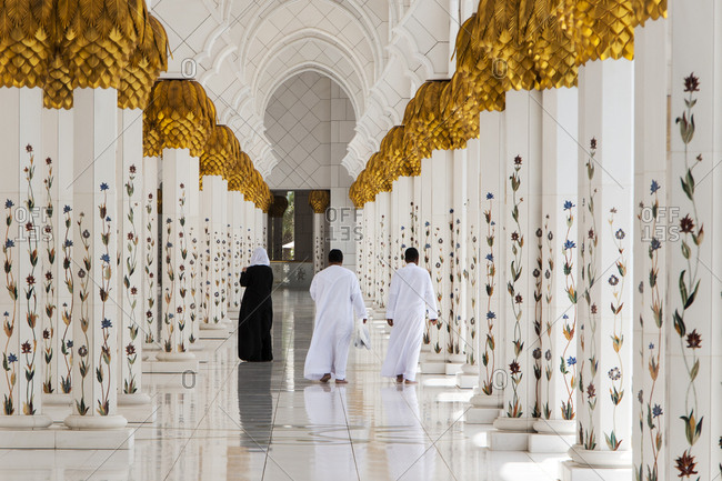 Abu Dhabi, United Arab Emirates - May 16, 2012: Visitors walk along a colonnaded passageway in the Sheikh Zayed Grand Mosque