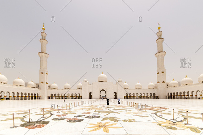 Abu Dhabi, United Arab Emirates - May 16, 2012: Visitors in the vast main courtyard of the Sheikh Zayed Grand Mosque