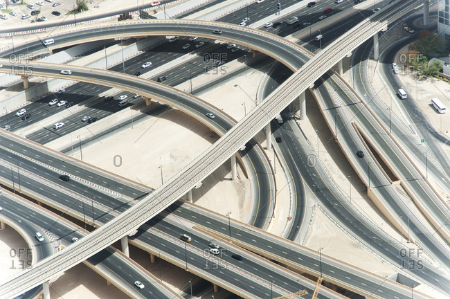 Aerial view of ribbons of asphalt intertwining as elevated roads, highway and metro line cross in Dubai, United Arab Emirates