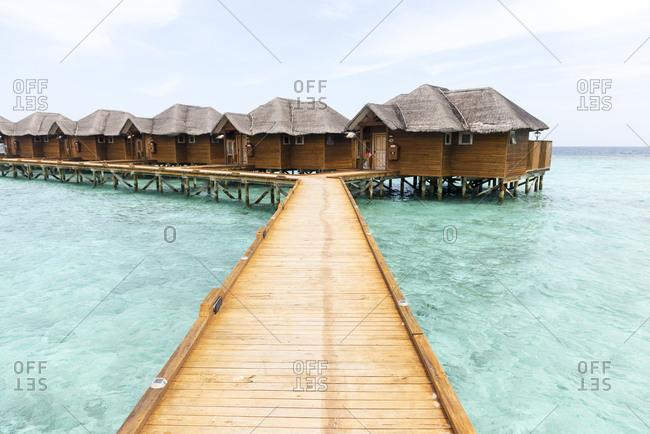 Fihalholi, Maldives - September 17, 2012: Boardwalk leading to cabins on stilts over azure sea at a resort