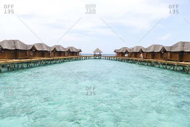 Fihalholi, Maldives - September 17, 2012: A man snorkels in the sea ringed by cabins on stilts at a resort