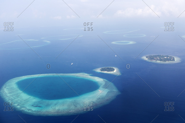 Aerial view of islands and atolls surrounded by deep blue seas in the Maldives