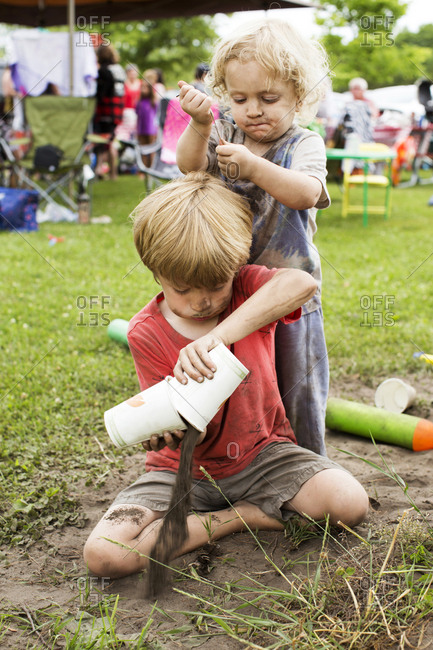Two brothers playing in the dirt outside at a festival