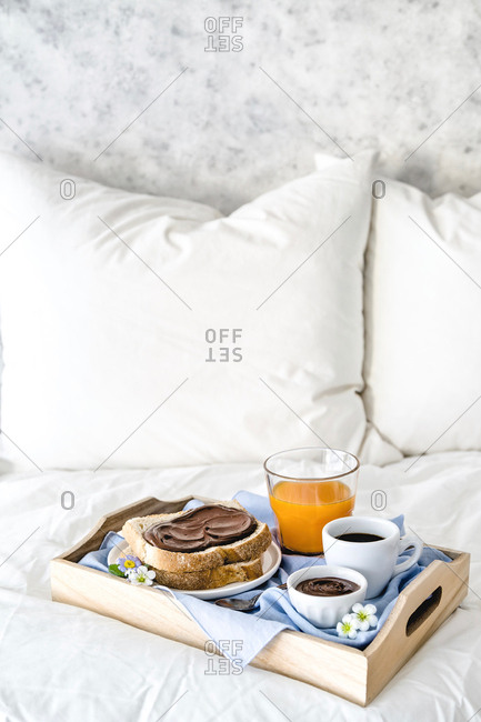 Breakfast tray of nibbled toast, chocolate spread and coffee on bed