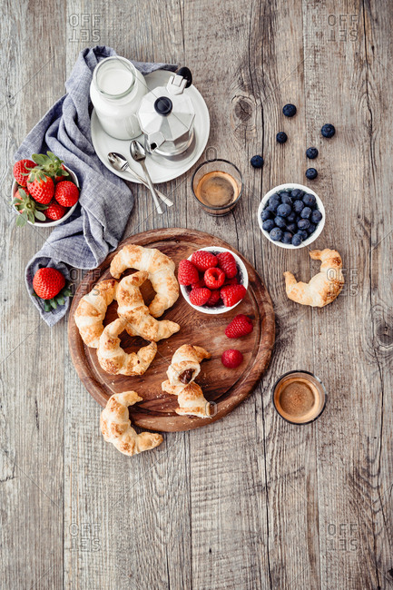 Breakfast with brioche, berries and coffee on wooden table