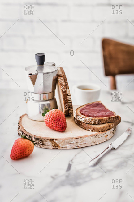 Breakfast with bread, berries jam and coffee on marble table