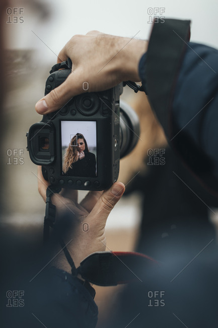 Photographer taking a picture of a woman whose image is displayed on the screen of a digital camera