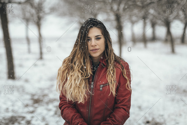 Portrait of woman wearing leather jacket standing alone in snow