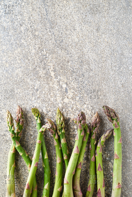 Close up of British asparagus laid out on stone surface